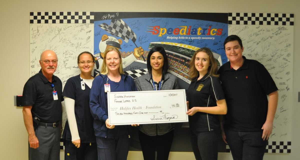 Picture of Sierra Hinzman, Father Lopez Catholic High School senior presenting a check to Halifax Health-Foundation board members and and Halifax Health Medical Center's Pediatric nurses
