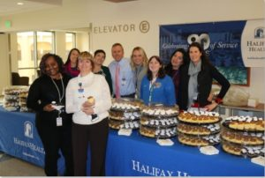 Picture of Halifax Health team members around a table with cupcakes