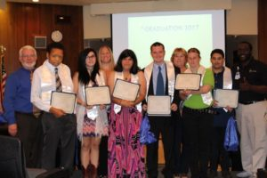 Picture of eight Project SEARCH students with High School Diplomas at Graduation Event at Halifax Health