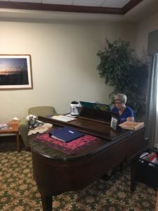 Picture of Regina Pritchard sitting at a beautiful Schafer & Sons Piano she donated to Halifax Health