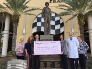 Picture of Halifax Health-Foundation board members, general manager for Tanger Outlets, Daytona Beach, Halifax Health Oncology Operations coordinator, Halifax Health Oncology chief therapist, and Halifax Health Chief Medical Physicist accepting check donated to Halifax Health-Foundation