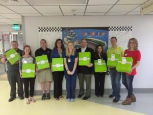 Employees representing LabCorp, Cheeriodicals, and Two Men And A Truck stand with gift boxes in Speediatrics