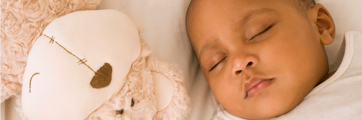 baby sleeping next to stuffed bear