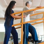 Photo of A senior latin woman going up a ramp during physical rehab, and being helped by a female physical therapist.