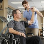 Image of A female physical therapist evaluating the range of motion of a male patient's shoulder. The patient is sitting in a wheelchair.