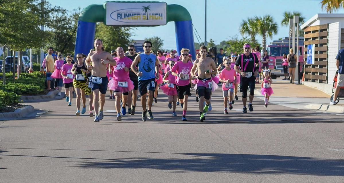 Image of runners at the 2nd Annual Pink Tutu 5K. Several runners wearing pink attire with the blow up start finish line behind them.