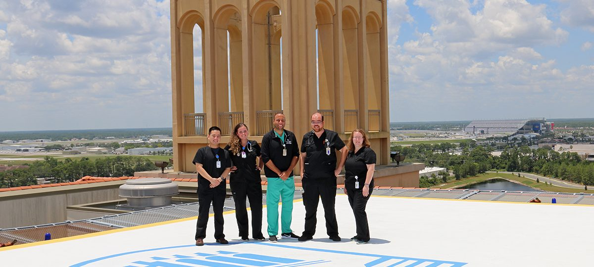 Photo of group of smiling Halifax Health team members atop helipad