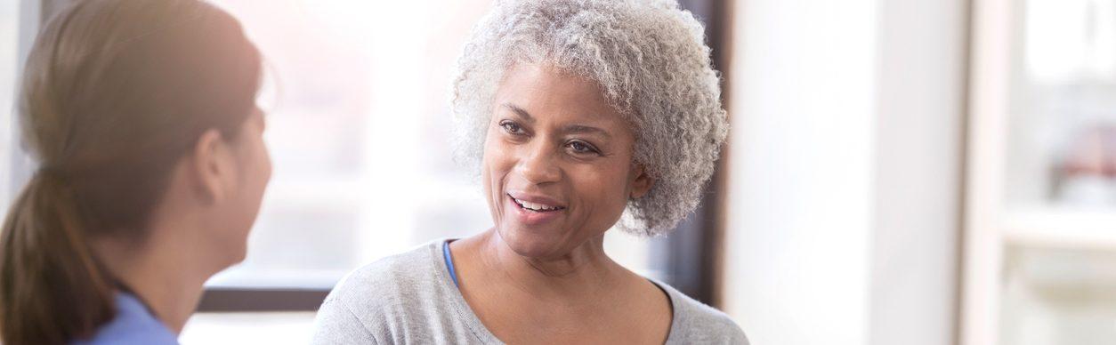 Cheerful senior woman talks with physician