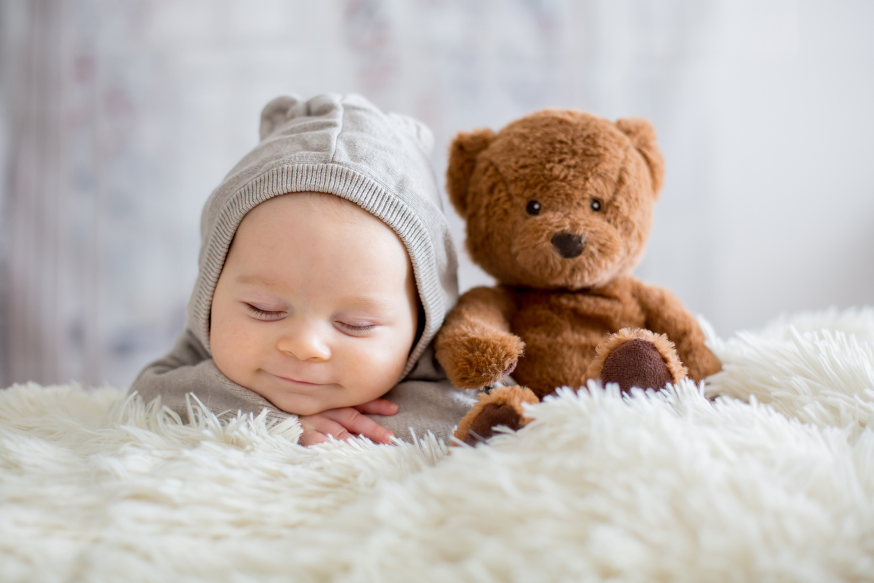 Sweet baby boy in bear overall, sleeping in bed with teddy bear; Halifax Health Pediatrics