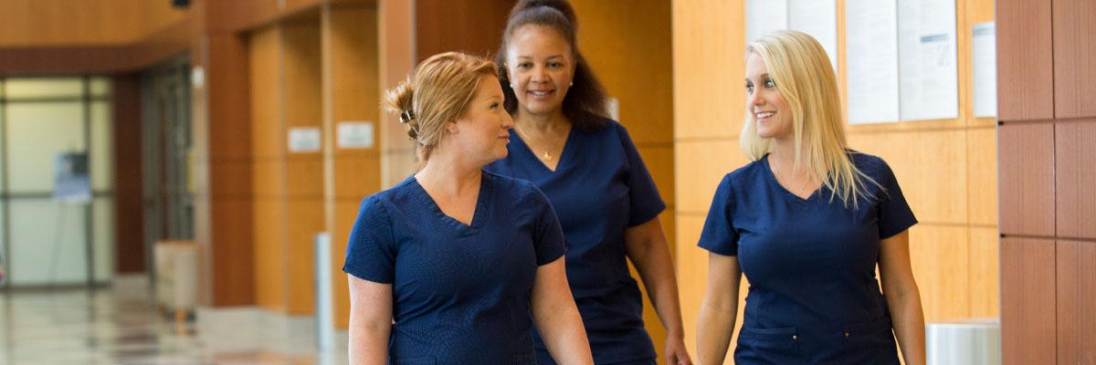 Image of three Halifax Health Nurses walking down hallway laughing